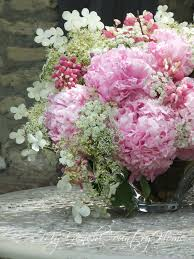 peony blooms with sprigs of climbing hydrangea a few branches of