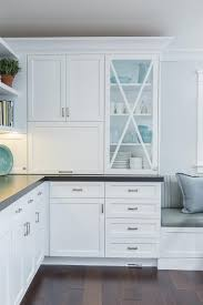 glass front kitchen cabinets with x trim moldings transitional