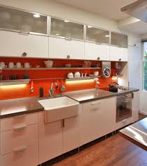 industrial kitchen idea in dc metro with a farmhouse sink industrial kitchen idea in dc metro with a farmhouse sink stainless steel appliances flat panel cabinets white cabinets and orange backsplash