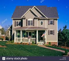 front view of a large brown two story house with white trim and a