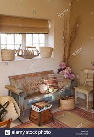 roman blind on window above painted wooden settle in cottage