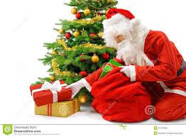 santa putting gifts under the christmas tree stock photo image