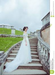 beautiful woman in vintage wedding dress stay on stairs stock