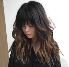 black hair with bangs and some ombré with beach waves