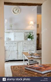 a staged lifestyle image of a white shabby chic dresser in a small