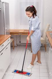 portrait of young maid in uniform cleaning kitchen floor stock
