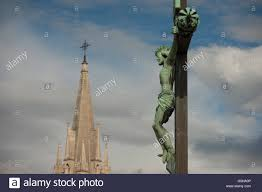 a crucified christ on the cross looking down on the tall spire of