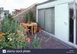 wooden table and chairs on paved roof garden of small loft