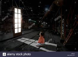 little kneeling in front of a lit window suspended in the air