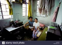 young married couple sit in their one room studio apartment in