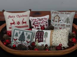 cross stitched christmas pillows displayed in a dough bowl i love