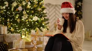 laughing woman in santa hat siting next to christmas tree and