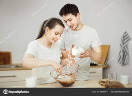 baisee dans sa cuisine homme et femme préparation de dessert sucré ensemble heureux