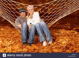 photo of young happy family lying down in hammock on backyard