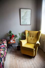 mustard velvet armchair pale floorboards grey walls and a