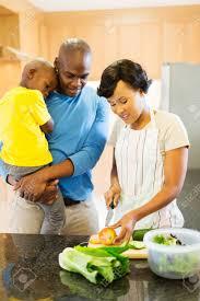 cuisine avec enfant femme africaine hacher les légumes avec mari et enfant dans la