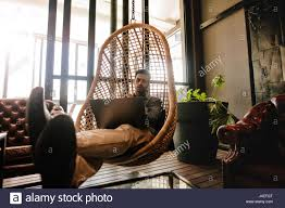 male executive sitting on a wicker hanging chair in office lounge