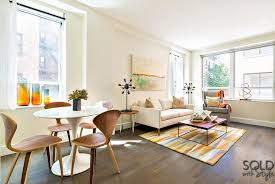 contemporary living room with hardwood floors by sold with style