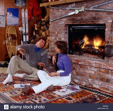 young couple sitting before a blazing fireplace in a ski cabin