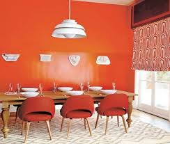 contemporary dining room with orange wall paint red chairs and