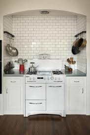 kitchen with white subway tile backsplash and wall mounted pot