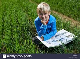 closeup of a child blond boy reading a book outside in a wheat