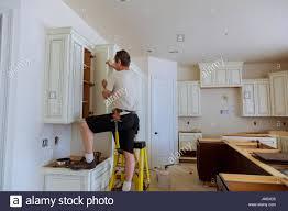 installation of kitchen worker installs doors to kitchen cabinet
