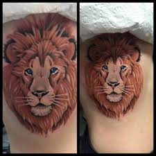 small lion face tattoo on rib