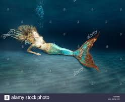 young mermaid laying in the sand at the bottom of the sea stock