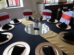 black tablecloth and napkins gold runner and chargers white