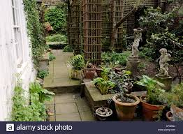 hidden treasure paved walkway arched trellis potted plants