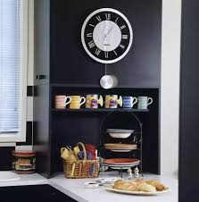 black and white kitchen framed pictures up of of clock on wall above colourful mugs on shelf