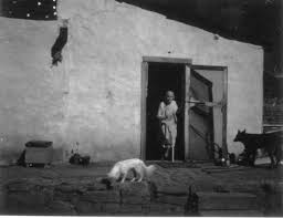 elderly woman in doorway of adobe house with two dogs boulder