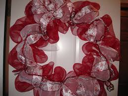 pink and red fabric ribbon christmas wreath on the door of