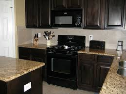 lovely kitchen with gray granite top also black kitchen appliances