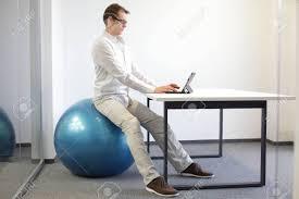 posture au bureau homme sur ballon de stabilité au bureau avec tablette