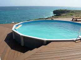 round pool with brown wooden pool deck above ground near blue sea