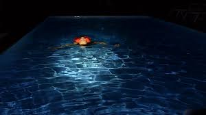 young swims in the pool at night slow motion stock video