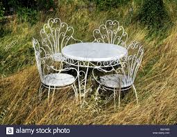 White Metal Chairs Outdoor White Metal Garden Table And Chairs In Overgrown Garden Stock