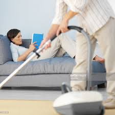young woman reading on the sofa and a man vacuuming stock photo