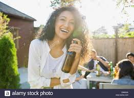 laughing woman drinking beer at backyard barbecue stock photo