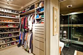corner walk in closet with white wooden shelving and shoe racks
