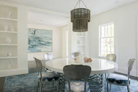 round white dining table with gray cascading chandelier
