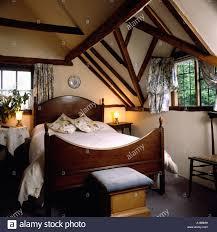 lighted lamps beside bed with wood headboard below dormer window