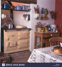 cream aga oven in white cottage kitchen with earthenware jars on