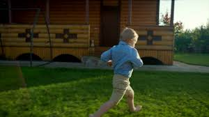 little boy running to his mom on the backyard at sunset stock