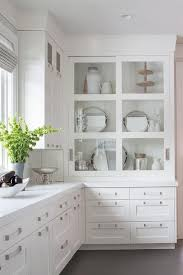 wall kitchen cabinet with glass doors in white white drawers donning satin nickel pulls and a white quartz
