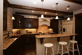 dark brown wooden kitchen cabinet added by three pendant lamps