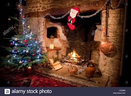 inglenook fireplace in old house with low burning log fire and