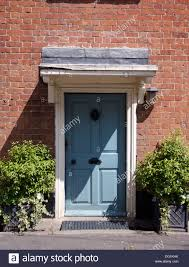 green shrubs in pots on either side of blue front door in brick